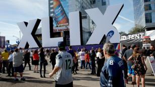 Des fans de football américain, mercredi 28 janvier 2015, devant le logo de la 49e édition du Super Bowl à Phoenix, dans l'Arizona.