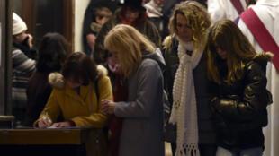 Des habitants de Saint-Féliu-d'Avall signent, le 15 décembre 2017, le livre d'or ouvert en hommage aux victimes de la collision.