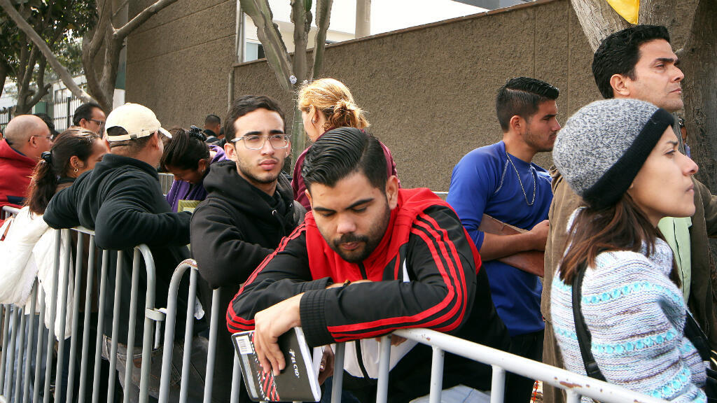Migrantes venezolanos esperan afuera de la sede de la Interpol para obtener el papeleo necesario para obtener un permiso de residencia temporal, en Lima, Perú, el 17 de agosto de 2018.