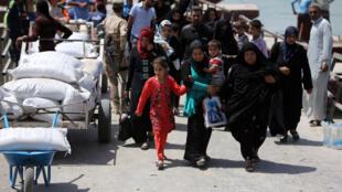 Des sunnites irakiens fuyant les violences arrivent aux abords de Bagdad, le 19 avril.