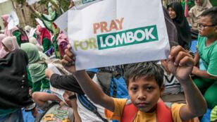"""Un enfant tient une pancarte où est écrit """"Priez pour Lombok"""" lors d'une évacuation de sinistrés à Medan, sur l'île indonésienne de Sumatra, le 8 août 2018."""