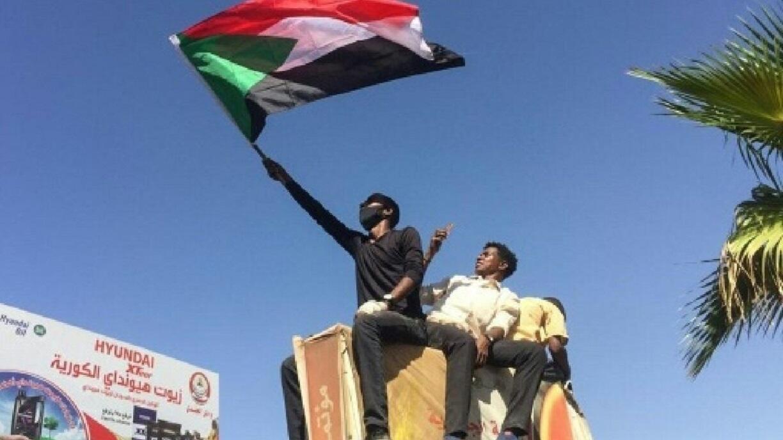 متظاهر يرفع العلم السوداني خارج مقر القيادة العامة للجيش في الخرطوم - 7 أبريل/نيسان 2019