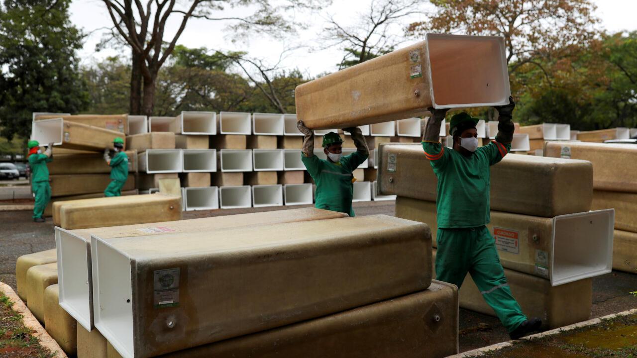 Estos hombres cargan las cajas que se instalarán a los ataúdes en el cementerio municipal de São Pedro, en São Paulo, Brasil, el 14 de mayo de 2020 y en medio del incremento de muertos por la pandemia del Covid-19.