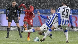 L'attaquant français du Bayern Munich, Kingsley Coman (c), tire et marque lors du match de Bundesliga sur la pelouse du Hertha Berlin, le 5 février 2021