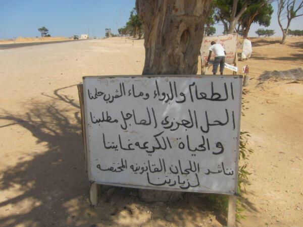 """""""La nourriture, les médicaments, l'eau potable, c'est notre rêve. Tout ce qu'on veut, c'est une vie normale. Nous invitons les instances juridiques à venir nous rendre visite"""", peut-on lire sur le panneau installé par les réfugiés près du poste frontière de Ras Jadir."""
