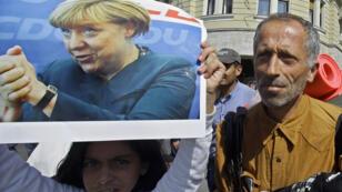 Une jeune migrante brandit une photo d'Angela Merkel dans le centre-ville de Budapest le 4 septembre 2015.