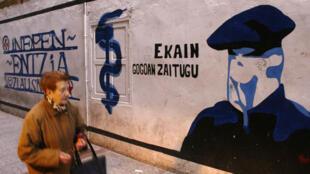 Archivo: una mujer pasa frente a una pintura mural que representa el logo del grupo ETA y honra a un activista que murió cuando la bomba que iba a plantar explotó y lo mató a él y a otros dos miembros de ETA en marzo de 2006.