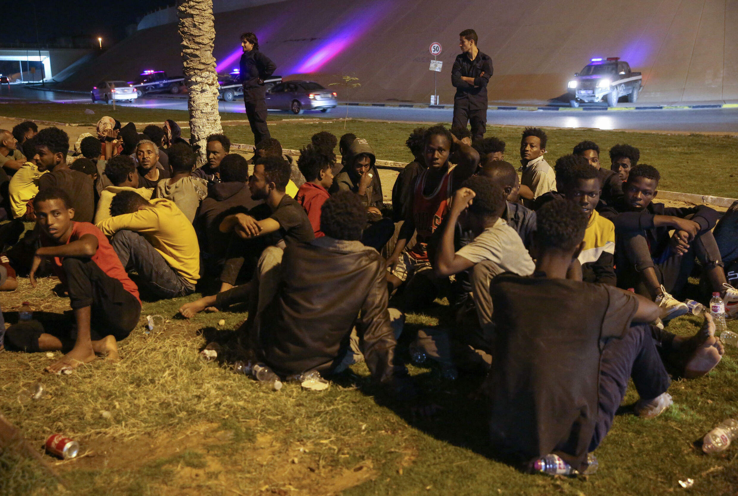 Migrants sit on the ground after being recaptured by Libyan security forces following an escape attempt from a detention facility in the capital Tripoli, on October 8, 2021