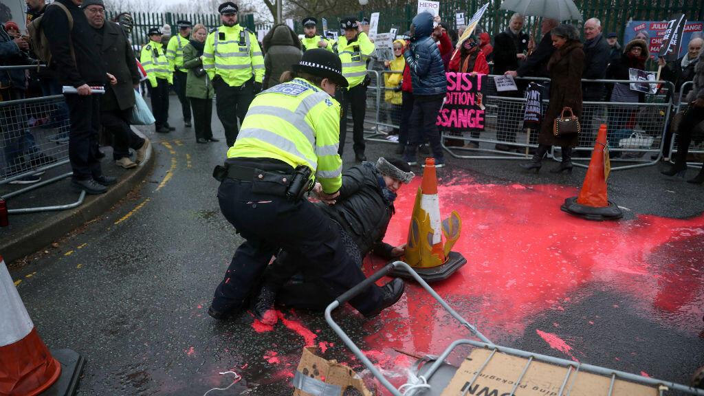 Un oficial de policía inmoviliza a una mujer después de que derramara pintura roja durante una manifestación en apoyo del fundador de WikiLeaks, Julian Assange, en Londres, Gran Bretaña, el 24 de febrero de 2020.