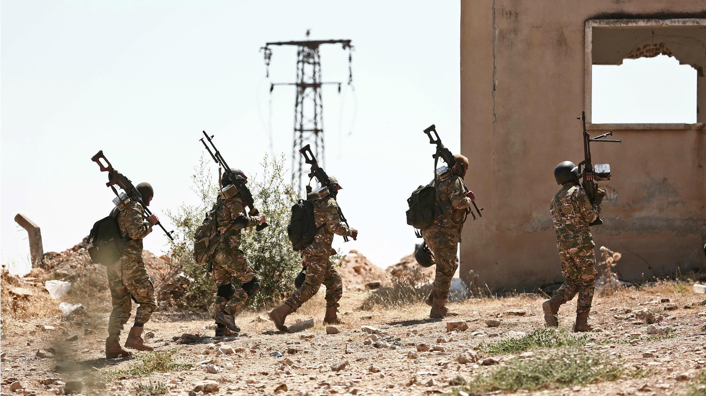 Combatientes del Frente de Liberación Nacional llevan sus ametralladoras mientras se preparan frente a un inminente ataque del Gobierno, cerca de Idlib, el 3 de septiembre de 2018.