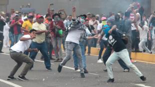 Manifestantes lanzan piedras y esquivan gases lacrimógenos en una protesta contra el Gobierno de Honduras en Tegucigalpa. 31 de mayo de 2019.