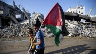 Palestinian boys walk past destroyed homes in the Shejaiya neighborhood of Gaza City in August 2014.