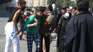 Des manifestants irakiens aident un homme blessé lors des manifestations antigouvernementales qui ont lieu sur la place Al Wathba, à Bagdad, le 31 janvier 2020.