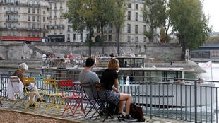 In this photo taken on October 12, 2018, people sit at café tables on the bank of the Seine River in Paris, France.