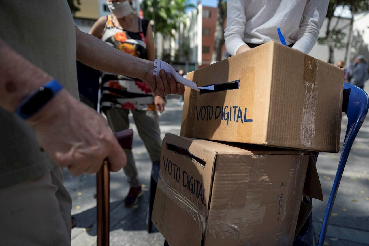 Un hombre deposita su código de votación digital durante la jornada votación presencial de la consulta popular impulsada por el opositor Juan Guaidó hoy, en Caracas (Venezuela).