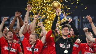 حارس مرمى الدانمارك نيكلاس لاندين جاكوبسن (يمين) يرفع الكأس بعد المباراة النهائية لبطولة العالم لكرة اليد للرجال 2021 بين الدانمارك والسويد في الصالة الرياضية باستاد القاهرة في العاصمة المصرية يوم 31 كانون الثاني/يناير 2021.