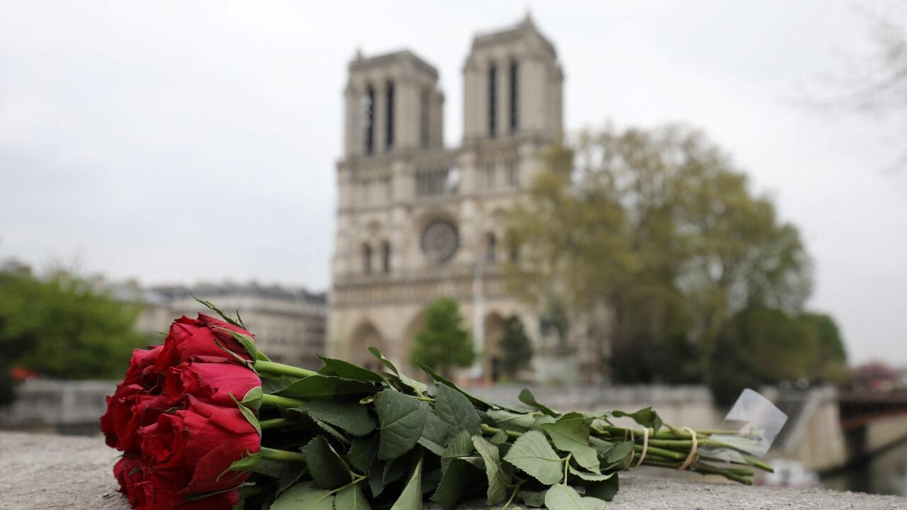 In this file photo taken on April 16, 2019, roses have been laid near Notre-Dame Cathedral in Paris, a day after it was devasted by a fire.