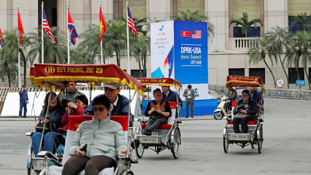 Los rickshaws transportan a los turistas junto a una señal para la próxima cumbre entre Corea del Norte y los Estados Unidos, cerca del hotel Metropole en Hanoi, Vietnam, el 25 de febrero de 2019.
