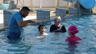 Iraqi swimming coach Omar Ibrahim trains girls at a swimming pool in Mosul on August 13, 2018