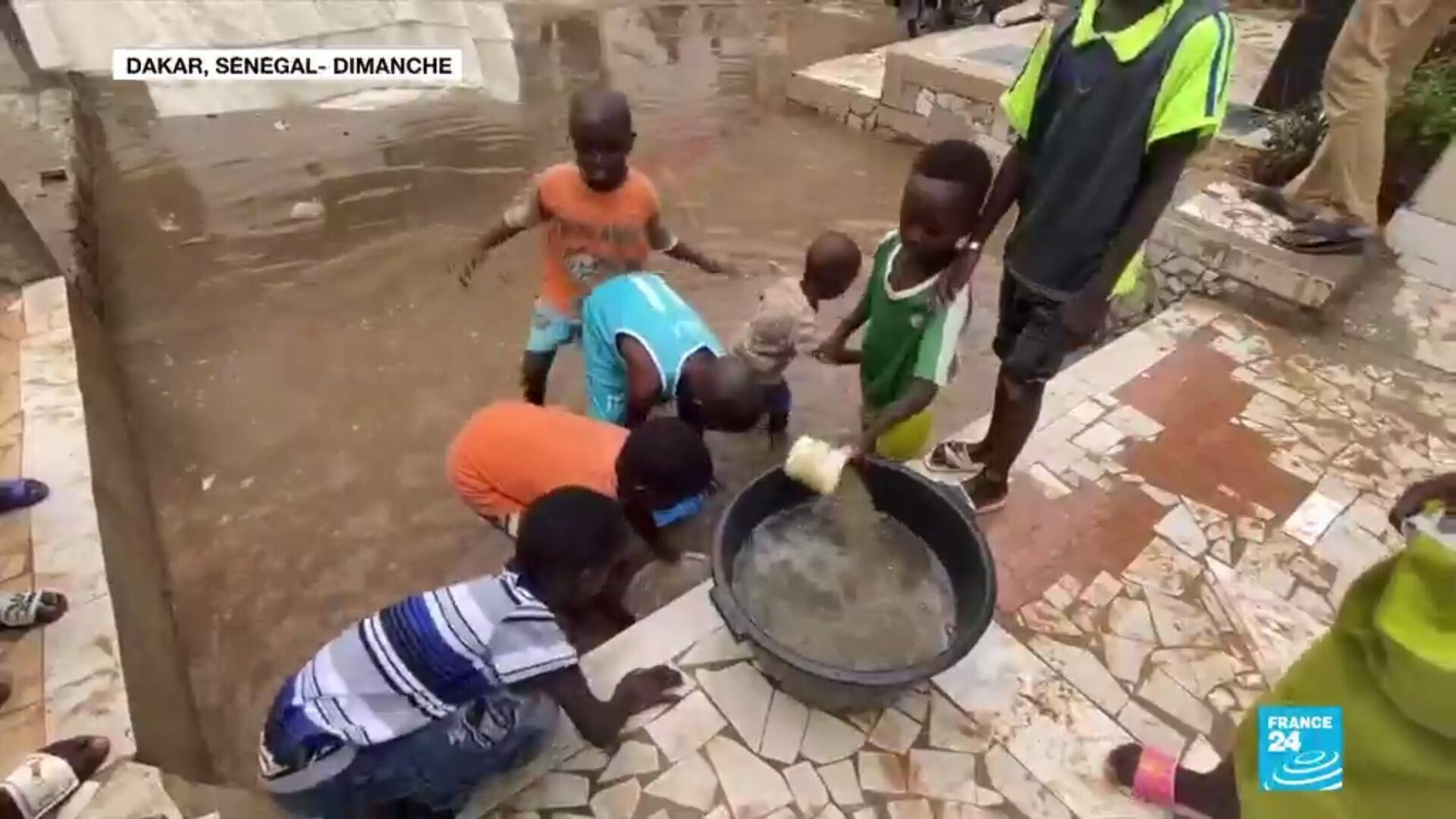 Des enfants écopent les eaux qui ont envahi leur quartier de Dakar après les inondations qui ont frappé le Sénégal, les 5 et 6septembre2020.