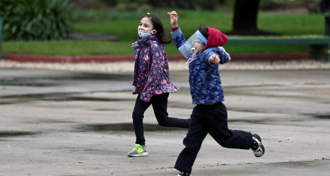 Niños con protectores faciales juegan en un parque mientras el Gobierno comienza a aliviar las restricciones de cuarentena impuestas para retrasar la propagación del coronavirus. Buenos Aires, Argentina, el 23 de julio de 2020.