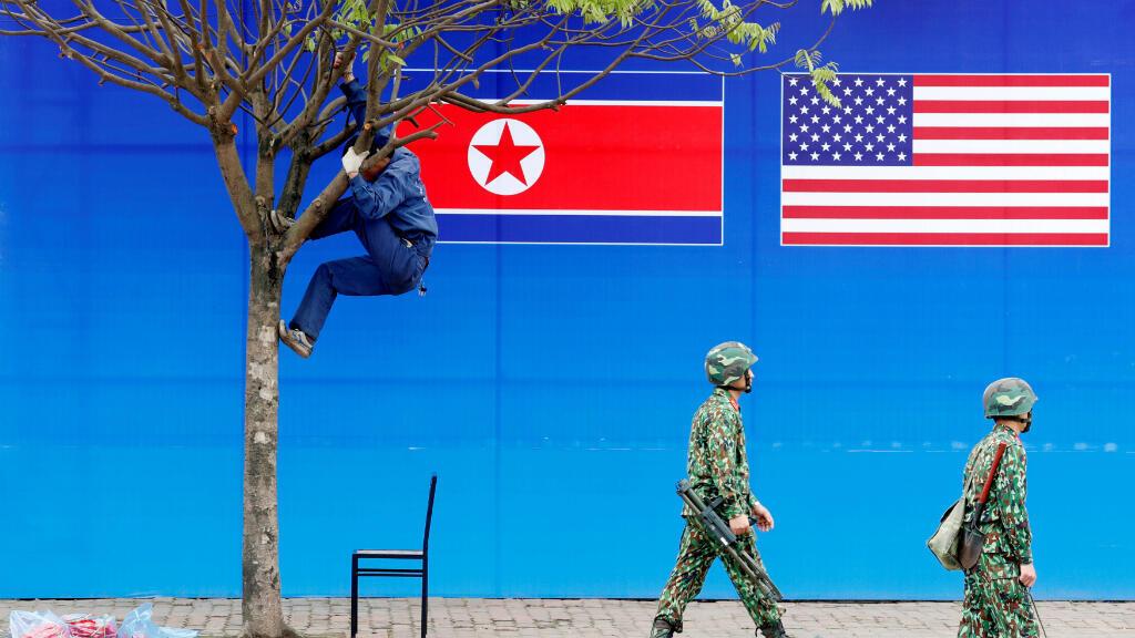 Se ve a un trabajador en un árbol al lado de una pancarta que muestra banderas de Corea del Norte y Estados Unidos antes de la cumbre Corea del Norte-Estados Unidos en Hanoi, Vietnam, el 25 de febrero de 2019.