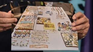 أحد رجال الشرطة الماليزية يعرض عددا من القطع التي تمت مصادرتها من رئيس الوزراء السابق نجيب عبد الرزاق في كوالالمبور في 27 يونيو 2018