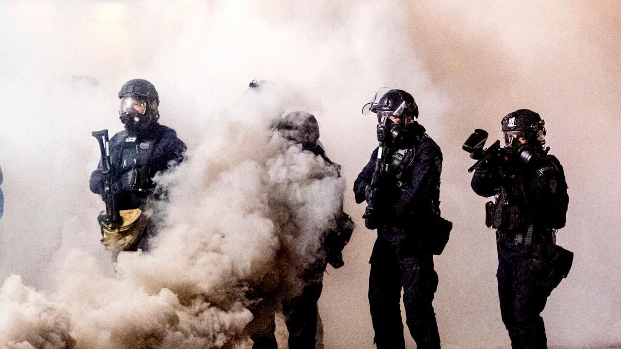 Varios agentes federales aparecen rodeados de gases lacrimógenos durante las protestas raciales en Portland, Estados Unidos, el 24 de julio de 2020.