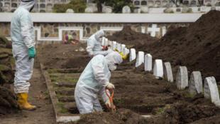 Trabajadores con equipo de bioseguridad en el cementerio de San Diego, en Quito, el 21 de julio de 2020