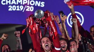 قائد ليفربول جوردان هندرسون (وسط) رافعا كأس الدوري الانكليزي الممتاز ومحتفلا مع زملائه. 22 تموز/يوليو 2020