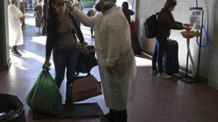 Trabajadores de la salud toman la temperatura a los pasajeros en la terminal de autobuses de Asunción, el 18 de mayo de 2020, después de que los servicios de transporte reanudaran su actividad, sólo por motivos de trabajo o situaciones de emergencia
