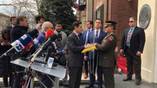 Carlos Vecchio, representante de Guaidó en EE. UU., entrega la bandera venezolana al coronel José Luis Silva tras tomar el control de la agregaduría militar naval y aérea el 18 de marzo de 2019 en Washington D.C.