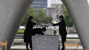 The list of names of war dead is given to Hiroshima City mayor Kazumi Matsui from a representative of families of the 1945 atomic bombing victims at Peace Memorial Park in Hiroshima, western Japan on August 6, 2020.