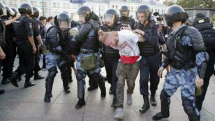 Des policiers anti-émeute arrêtent un manifestant lors d'un rassemblement non autorisé à Moscou, le 27 juillet 2019.