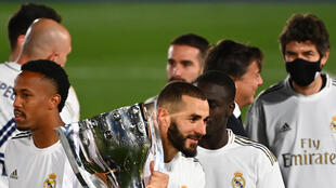 Benzema celebrates with the trophy Real clinched the title