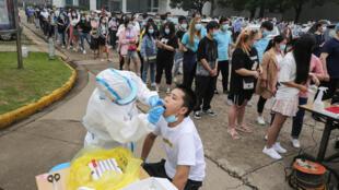 Des personnes font la queue pour se faire dépister, le 15 mai 2020 à Wuhan, en Chine, après l'apparition de nouveaux cas de Covid-19