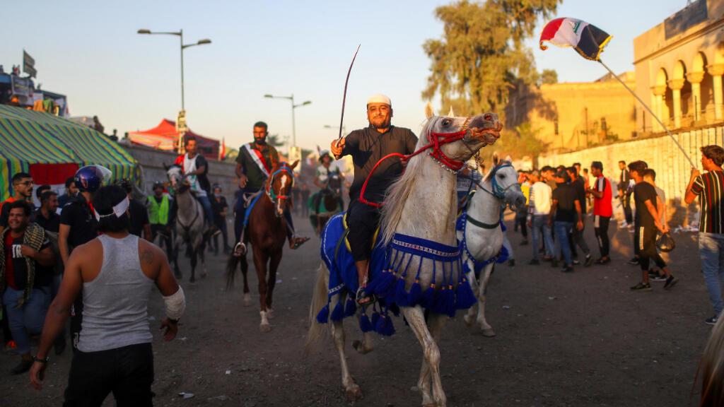Un manifestante iraquí agita su espada mientras monta un caballo durante las protestas antigubernamentales en Bagdad, Irak.