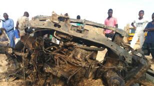 Un grupo de personas observan un vehículo destruido por los militares durante el fuego cruzado con los islamistas del Boko Haram en Maiduguri. 27 de abril, 2018.