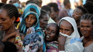 Ethiopian refugees queue for supplies at the Um Rakuba refugee camp, which houses refugees fleeing the fighting in Ethiopia's Tigray region, on the Sudan-Ethiopia border on November 29, 2020.
