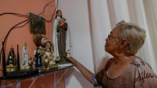 Maria Moitinho Nunes Sinimbú, de 76 años, madre de 12 hijos, organiza su altar con imágenes de santos católicos después de una entrevista con AFP sobre la muerte de tres de sus hijo por COVID-19, en su casa en el barrio de Sao Francisco en Manaos, estado de Amazonas, Brasil, el 16 de mayo de 2020.