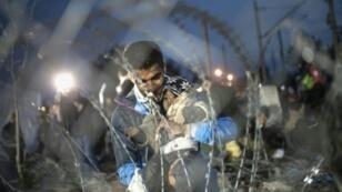 مهاجرون افغان خلف شريط شائك في غيفغيليا عند الحدود اليونانية المقدونية حيث تم منعهم من دخول مقدونيا 22 فبراير 2016