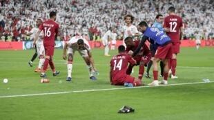 اللاعبون القطريون يحتفلون بثالث أهدافهم في مرمى الإمارات، والجمهور الإماراتي يرمي الأحذية وزجاجات المياه عليهم