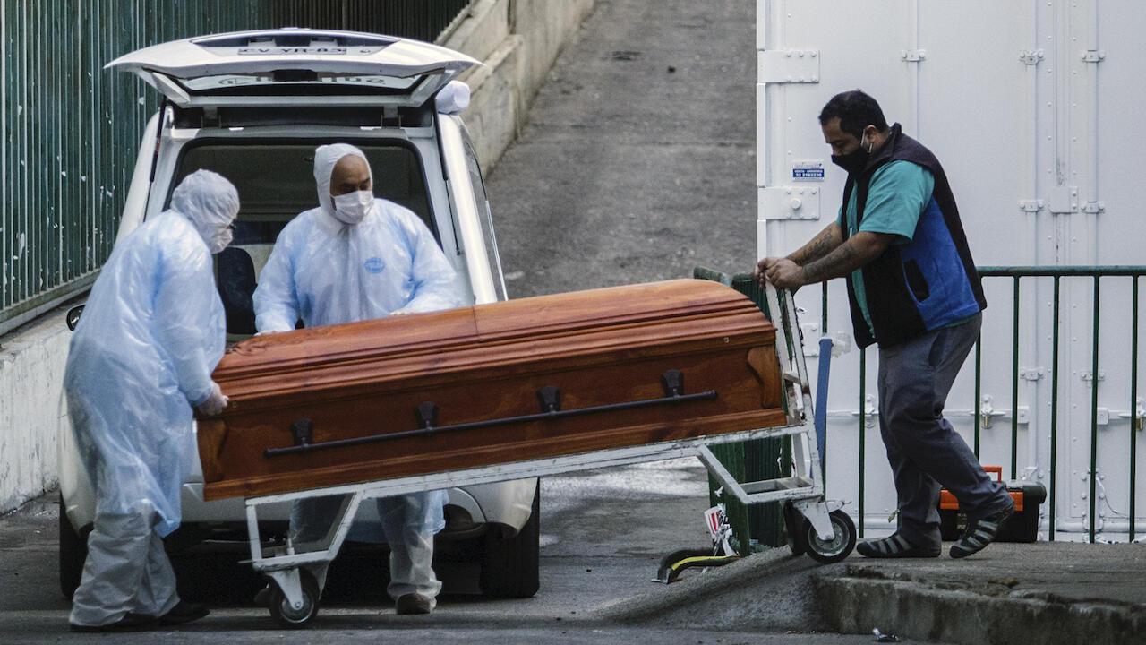 Los empleados de una funeraria llevan el 12 de junio de 2020 el ataúd de una persona que murió por Covid-19 en Valparaíso, Chile.