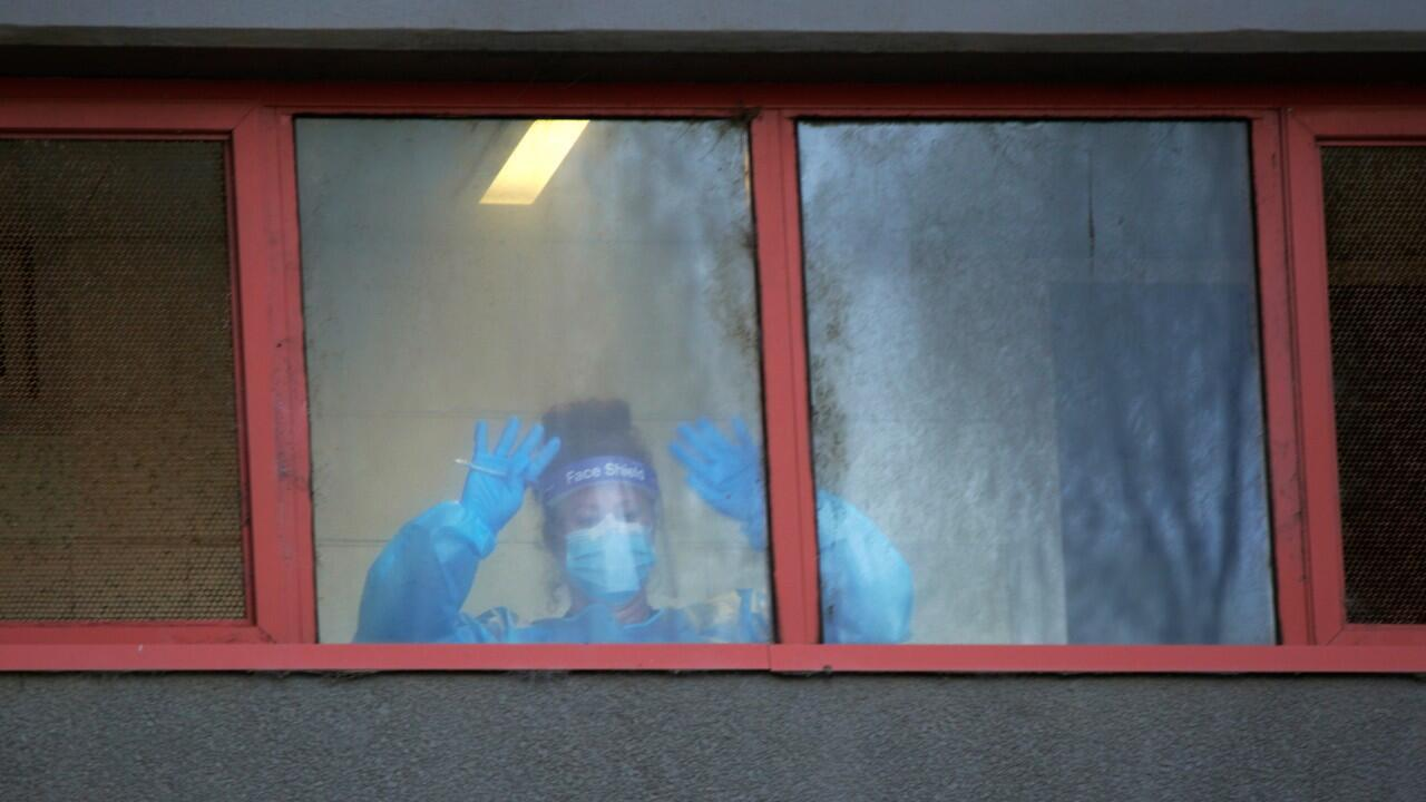 A healthcare worker signals to her colleagues from a window of a public housing tower, locked down in response to an outbreak of the coronavirus disease (COVID-19), in Melbourne, Australia, July 8, 2020.