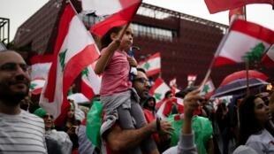 Los manifestantes ondean banderas nacionales libanesas durante el octavo día de protestas antigubernamentales en una carretera en Jal el-Dib, Líbano, 24 de octubre de 2019.