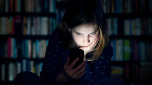 Foto dramatizada de una menor con su celular.