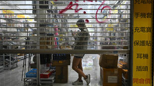 Un magasin baisse le rideau lors d'une manifestation pro-démocratie, dans le quartier de Kowloon à Hong Kong, le 20 octobre 2019.