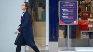 Une femme passe devant un panneau publicitaire à Pékin le 11 novembre 2015.