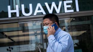Un hombre pasa frente a una tienda de Huawei mientras habla por teléfono móvil, el 25 de mayo de 2020 en Pekín