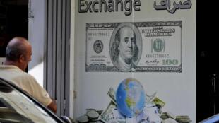 رجل جالس أمام مكتب صيرفة في بيروت في 1 تشرين الأول/أكتوبر 2019. ويشهد لبنان أزمة اقتصادية متصاعدة منذ فترة أدت مؤخراً إلى ارتفاع سعر صرف الليرة اللبنانية مقابل الدولار في السوق السوداء